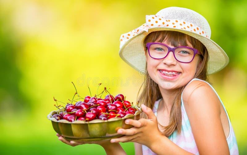 Criança com cerejas Menina com cerejas frescas Cintas e vidros vestindo dos dentes da menina loura caucasiano bonito nova fotos de stock