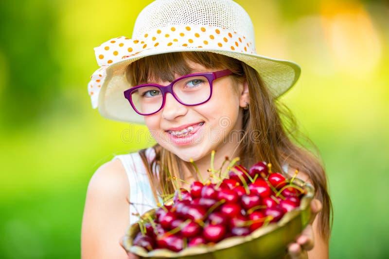 Criança com cerejas Menina com cerejas frescas Cintas e vidros vestindo dos dentes da menina loura caucasiano bonito nova fotos de stock royalty free