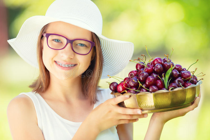 Criança com cerejas Menina com cerejas frescas Retrato de uma moça de sorriso com a bacia completa de cerejas frescas foto de stock