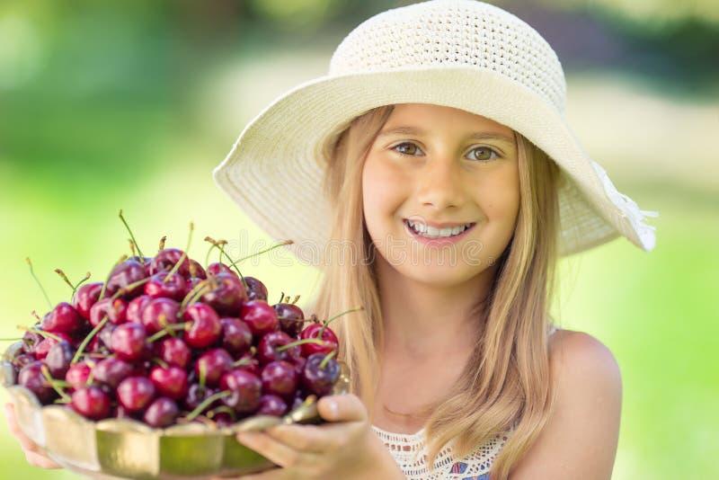 Criança com cerejas Menina com cerejas frescas Retrato de uma moça de sorriso com a bacia completa de cerejas frescas imagens de stock