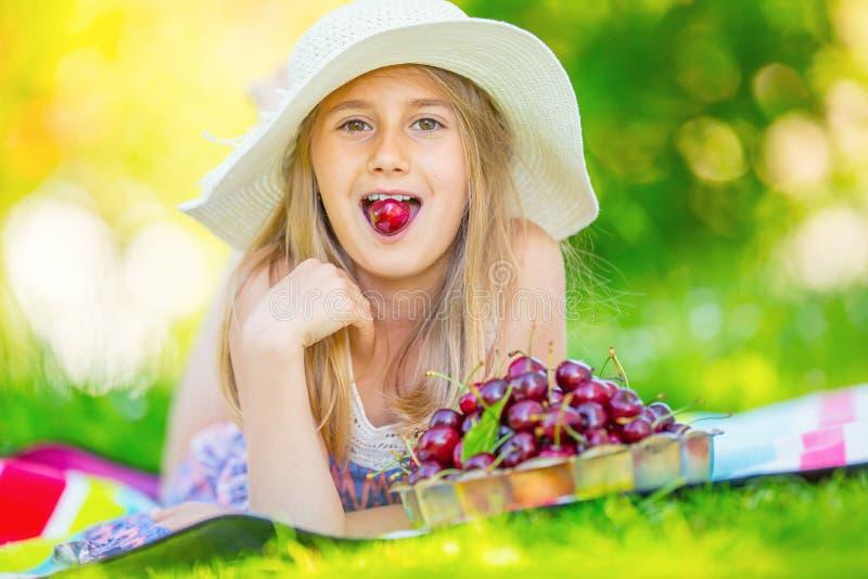 Criança com cerejas Menina com cerejas frescas Retrato de uma moça de sorriso com a bacia completa de cerejas frescas imagens de stock royalty free