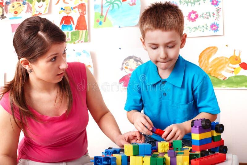 Criança com a construção ajustada no quarto do jogo. foto de stock