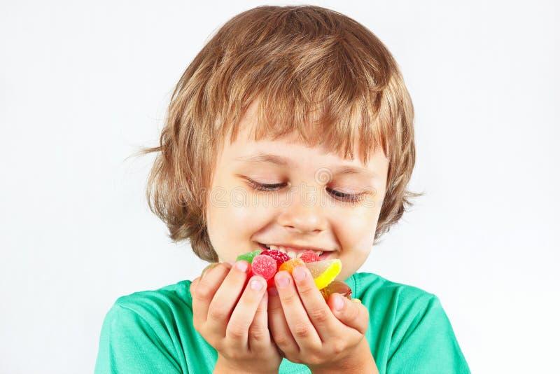 Criança com doces e os doces coloridos da geleia no fundo branco foto de stock