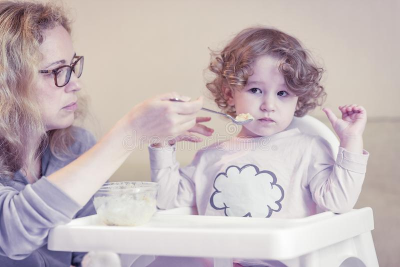 A criança com dois anos é impertinente e recusa comer fotos de stock royalty free