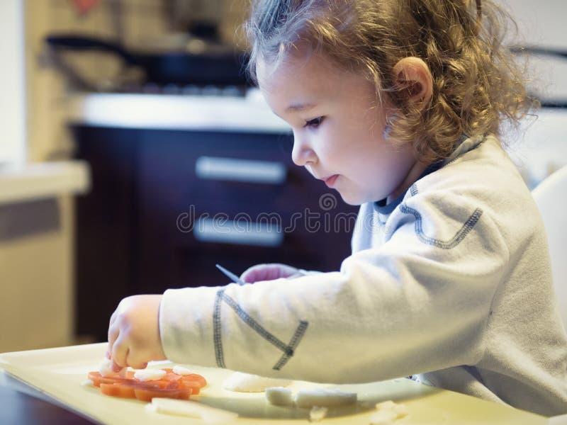 A criança com dois anos corta cenouras e batatas na cozinha fotografia de stock royalty free