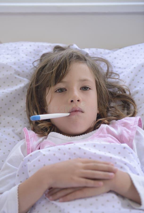 Criança com febre na cama fotografia de stock royalty free