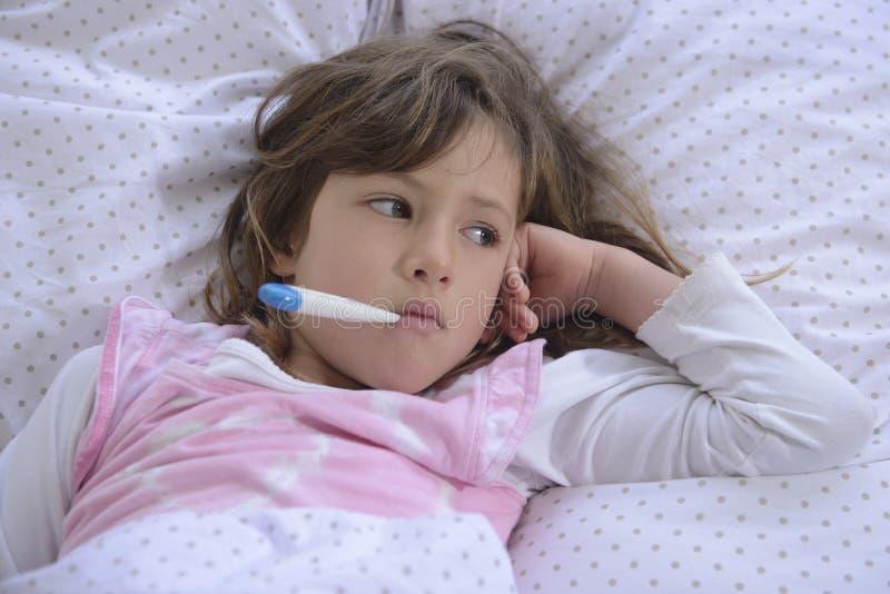 Criança com febre na cama foto de stock royalty free