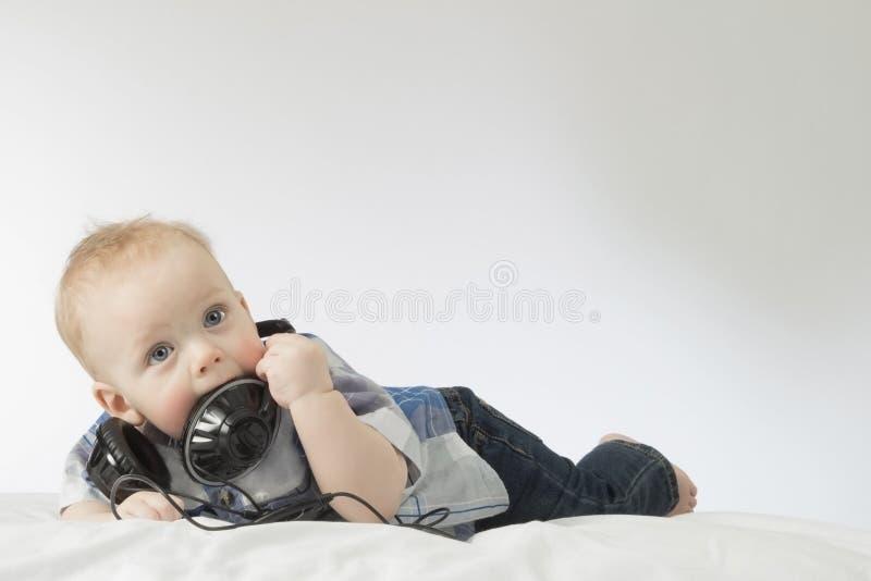 Criança com fones de ouvido Menino infantil de olhos azuis adorável na cama com os fones de ouvido em sua boca Tiro horizontal do imagens de stock royalty free