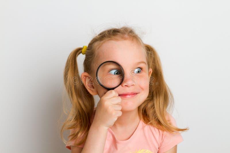 Criança com lente de aumento fotografia de stock royalty free