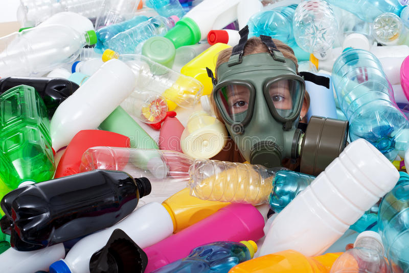 Criança com a máscara de gás coberta com as garrafas plásticas fotos de stock royalty free