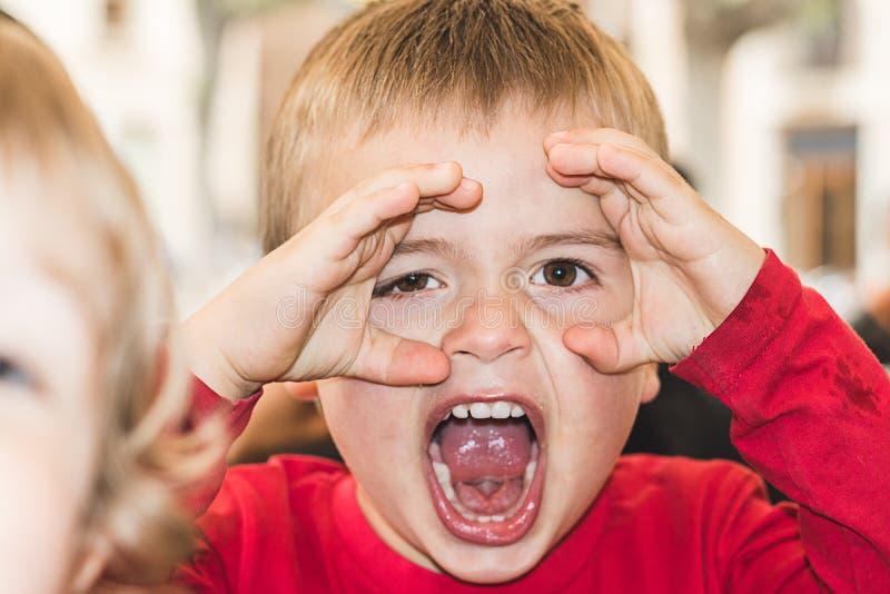 Criança com mãos nos olhos a observar fotografia de stock royalty free
