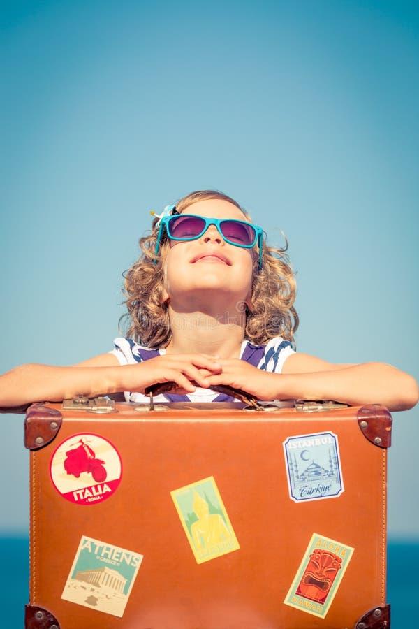 Criança com a mala de viagem do vintage em férias de verão fotografia de stock royalty free