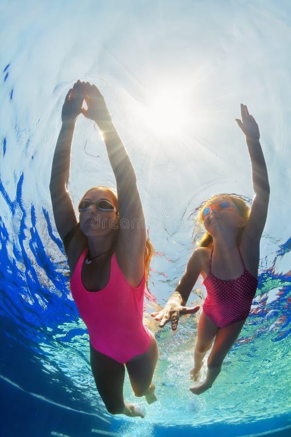 Criança com mergulho da mãe na piscina foto de stock