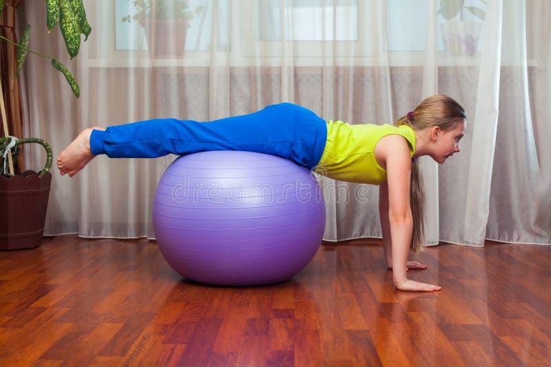 Criança com na bola para o fittnesa em casa fotos de stock