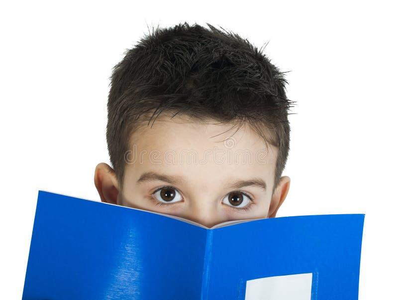Criança com o caderno na frente da cara fotos de stock royalty free