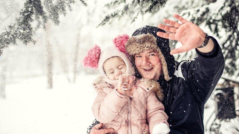Criança com o pai no parque do inverno Emoções positivas snowfall imagem de stock