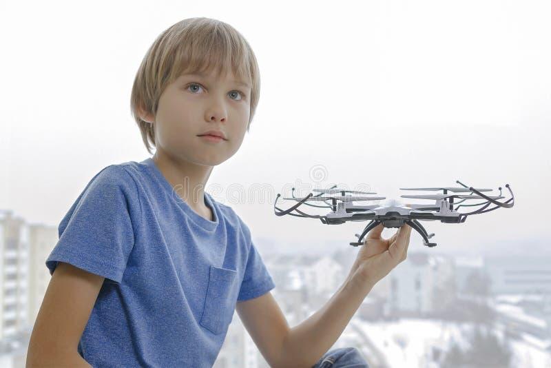 Criança com o zangão contra a janela em casa A tecnologia, lazer brinca o conceito imagem de stock