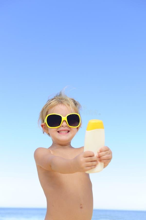 Criança com os óculos de sol que mostram o suncream fotos de stock royalty free