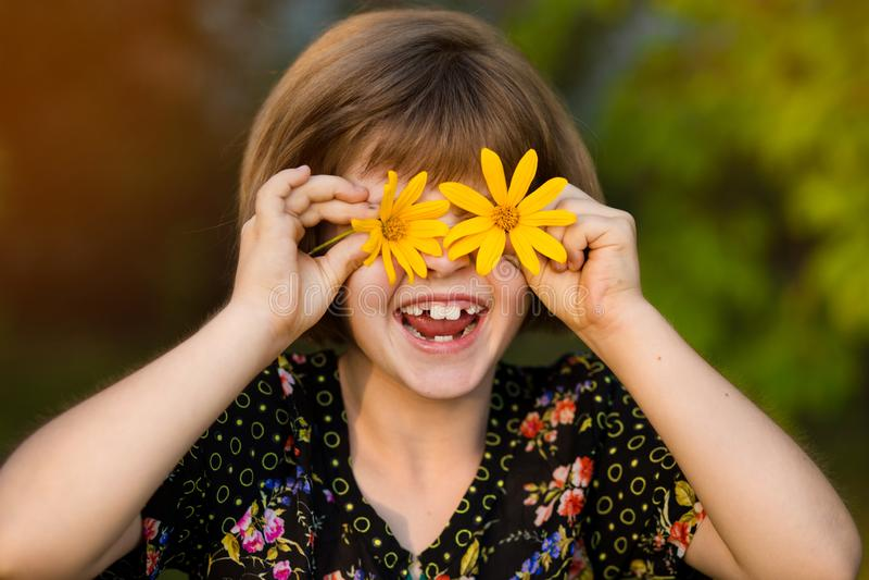 Criança com os olhos das flores no parque verde fotografia de stock