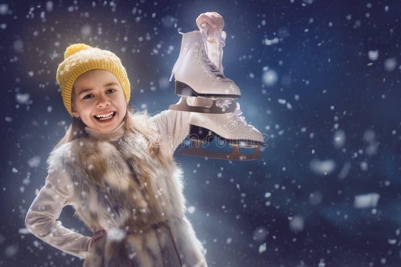 Criança com os patins no fundo escuro imagem de stock