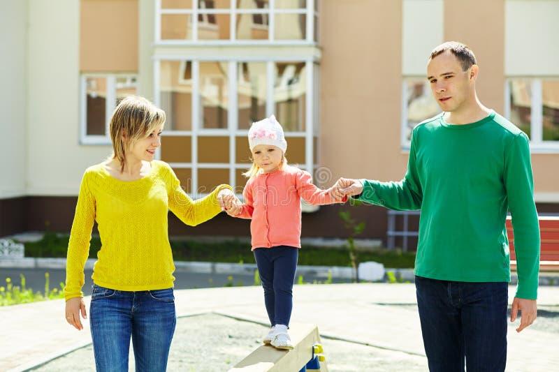 Criança com pais em um campo de jogos imagem de stock royalty free