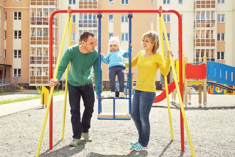 Criança com pais no campo de jogos foto de stock royalty free