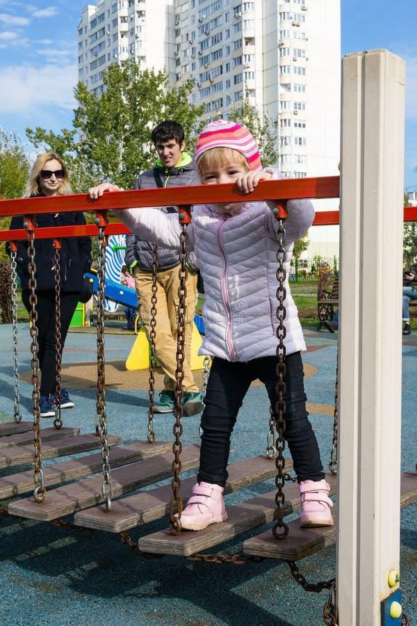 Criança com pais no campo de jogos fotografia de stock royalty free