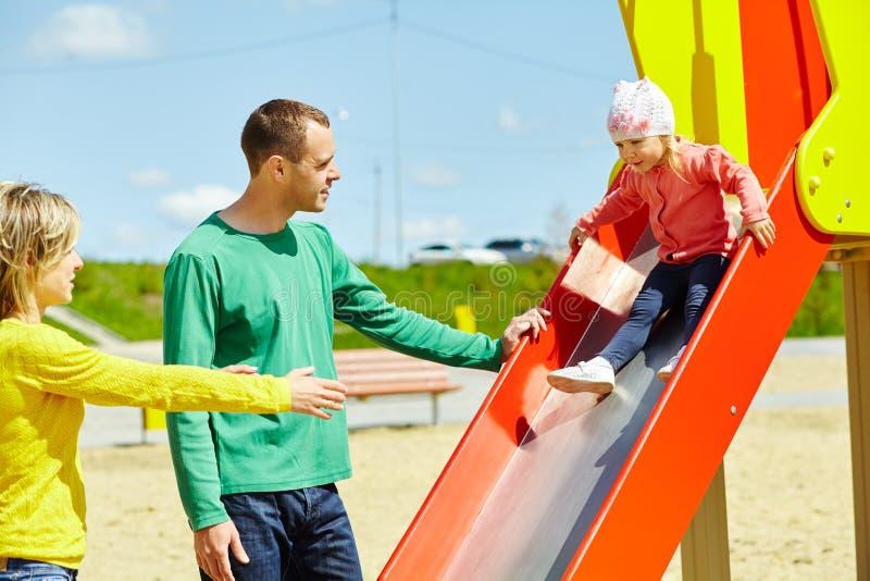 Criança com pais no campo de jogos exterior fotografia de stock royalty free