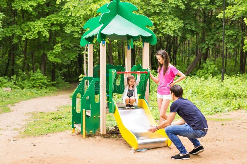Criança com pais no campo de jogos Mamã, paizinho e filha Jogando a família imagens de stock royalty free