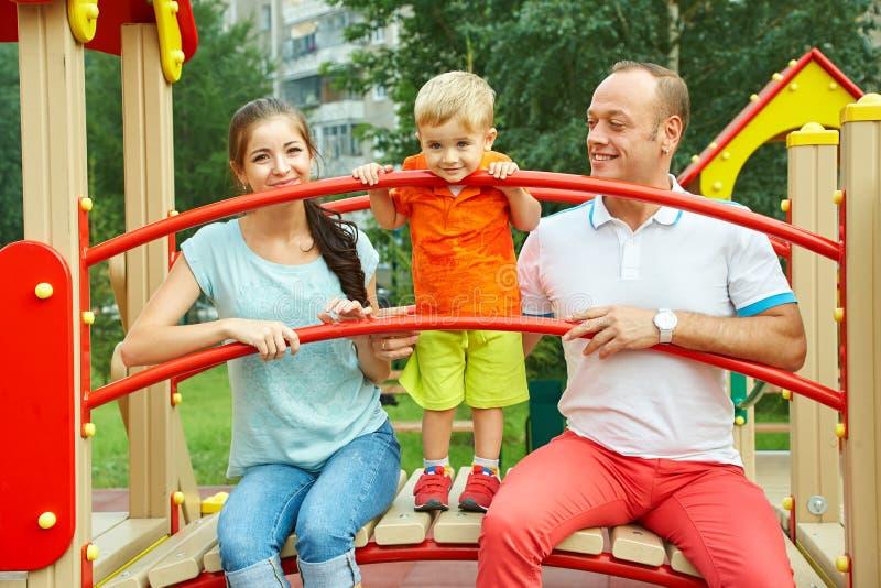 Crian?a com pais no campo de jogos Mam?, paizinho e filho Jogando a fam?lia imagem de stock royalty free