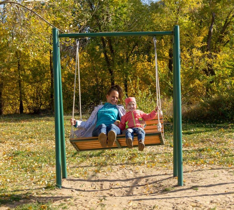 Criança com passeio da mamã em um balanço no outono imagem de stock