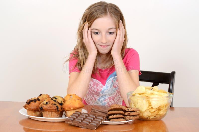 Criança com a pilha enorme da comida lixo imagem de stock
