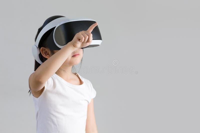 Criança com realidade virtual, VR, tiro do estúdio dos auriculares isolado no fundo branco Criança que explora o mundo virtual de imagem de stock