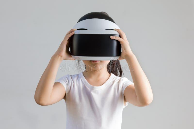 Criança com realidade virtual, VR, tiro do estúdio dos auriculares isolado no fundo branco Criança que explora o mundo virtual de fotografia de stock