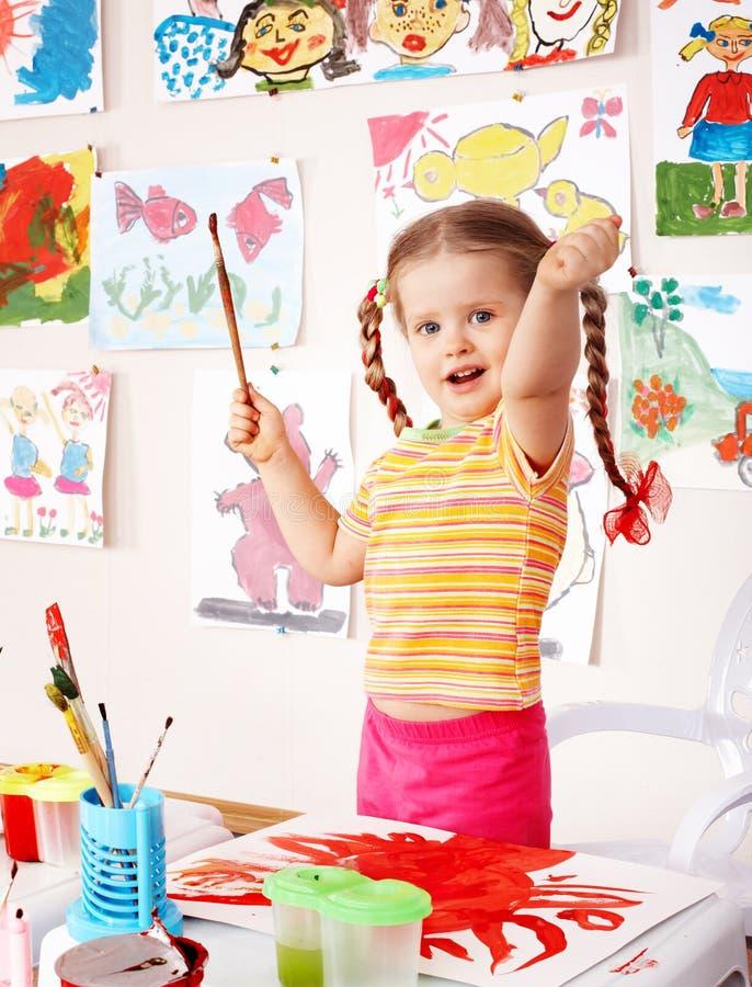 Criança com retrato e escova no playroom. imagem de stock royalty free