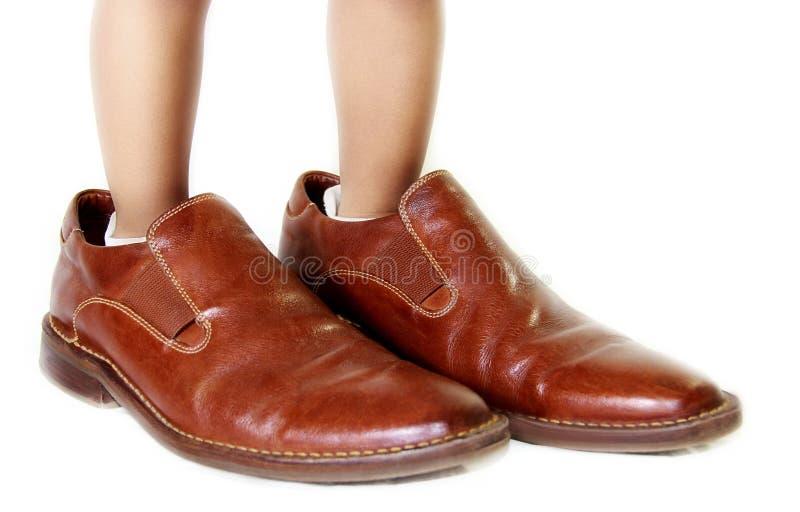 Criança com sapatas do paizinho fotografia de stock royalty free