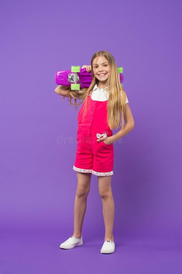 Criança com sorriso encantador isolada no fundo violeta Menina com cabelo louro no fato-macaco cor-de-rosa e nas sapatilhas branc fotos de stock royalty free