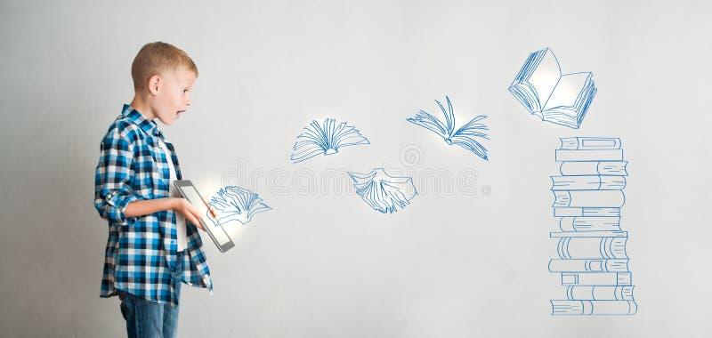 Criança com tabuleta e os livros digitais imagem de stock