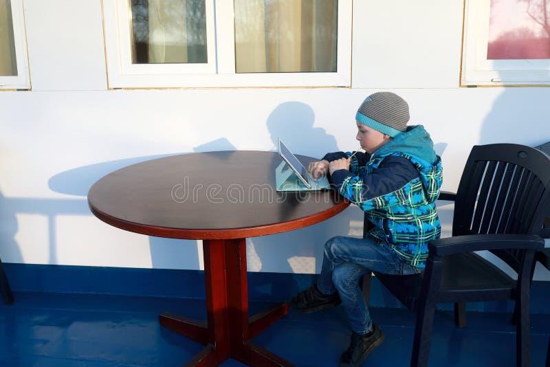 Criança com a tabuleta na tabela imagens de stock