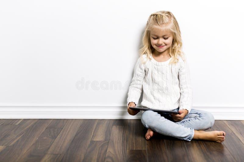 Criança com a tabuleta que encontra-se no assoalho Menina que joga o laptop imagem de stock royalty free