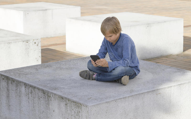 Criança com telefone Menino que olha a tela, jogando jogos, usando apps outdoor Lazer da tecnologia dos povos da escola imagem de stock royalty free