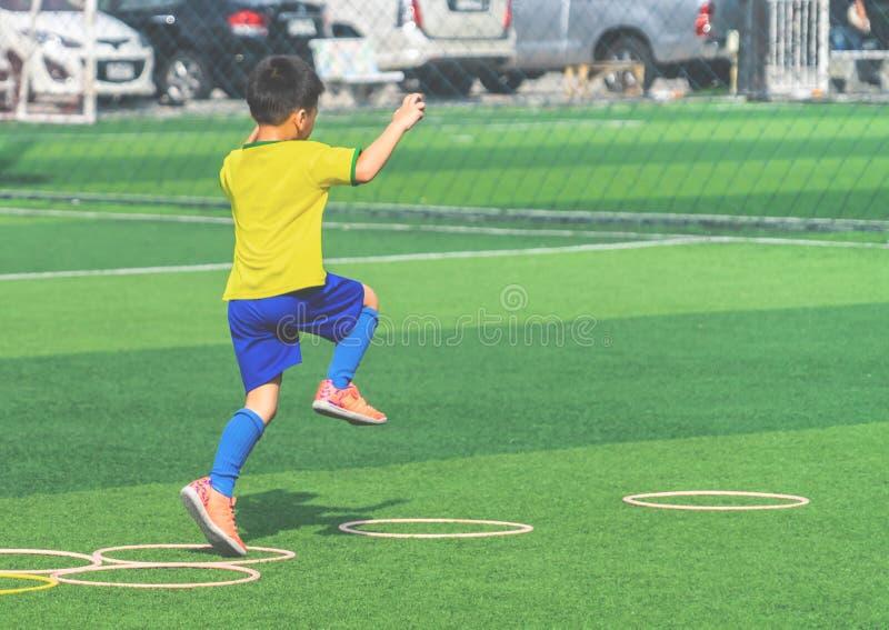 Criança com treinamento do futebol no círculo da velocidade da agilidade no treinamento do futebol fotografia de stock