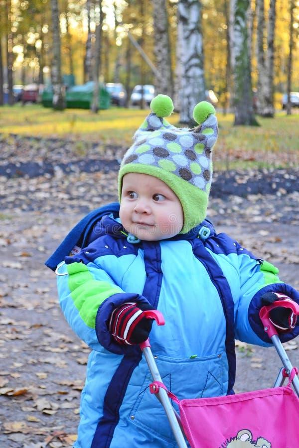 Criança com um carrinho de criança do brinquedo fotografia de stock