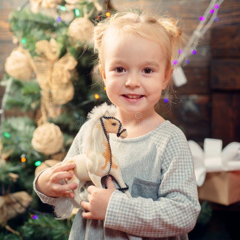 Criança com um presente de Natal no fundo de madeira Crianças felizes Crianças do ano novo criança Retrato da criança feliz foto de stock royalty free