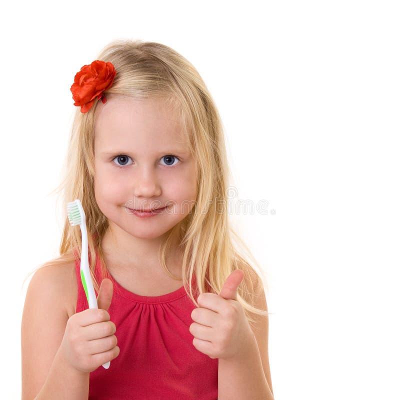 A criança com um toothbrush mostra os polegares acima imagem de stock royalty free
