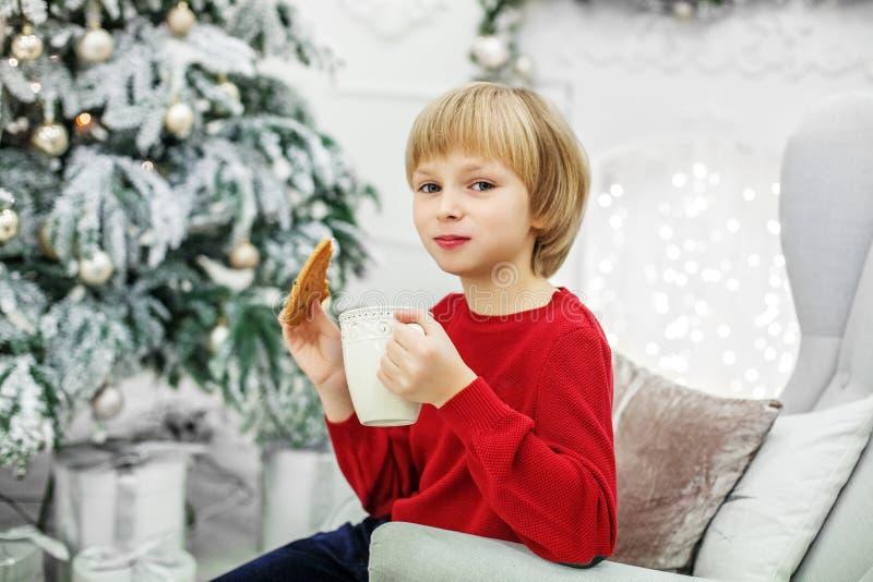 A criança come cookies e bebe o leite Menino O conceito de Chri imagens de stock