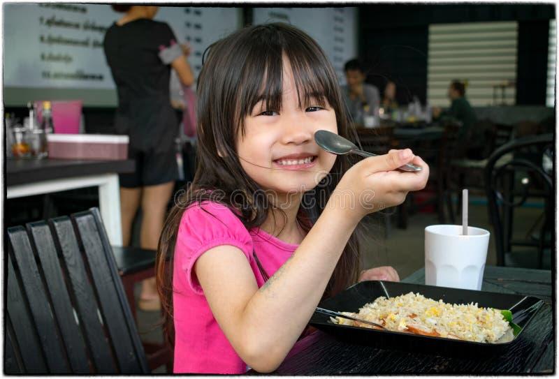 A criança come Fried Rice com uma colher em um asiático autêntico Restaura foto de stock royalty free