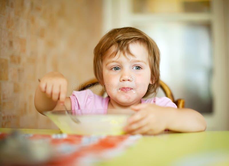 A criança come na casa fotografia de stock