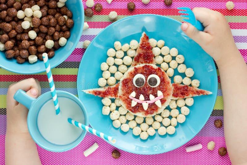 A criança come o café da manhã engraçado do brinde com o tubarão dado forma doce fotos de stock royalty free