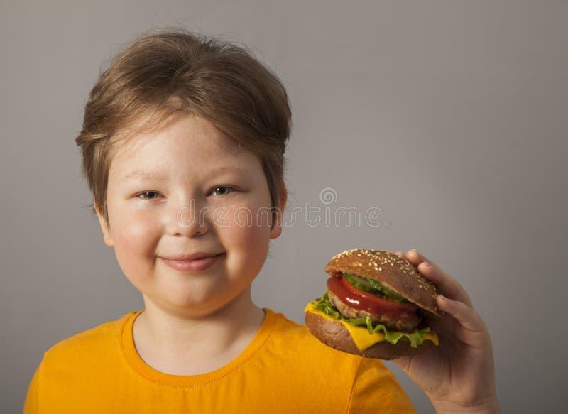 A criança come o hamburguer no fundo cinzento Criança masculina com Hamburger fotografia de stock